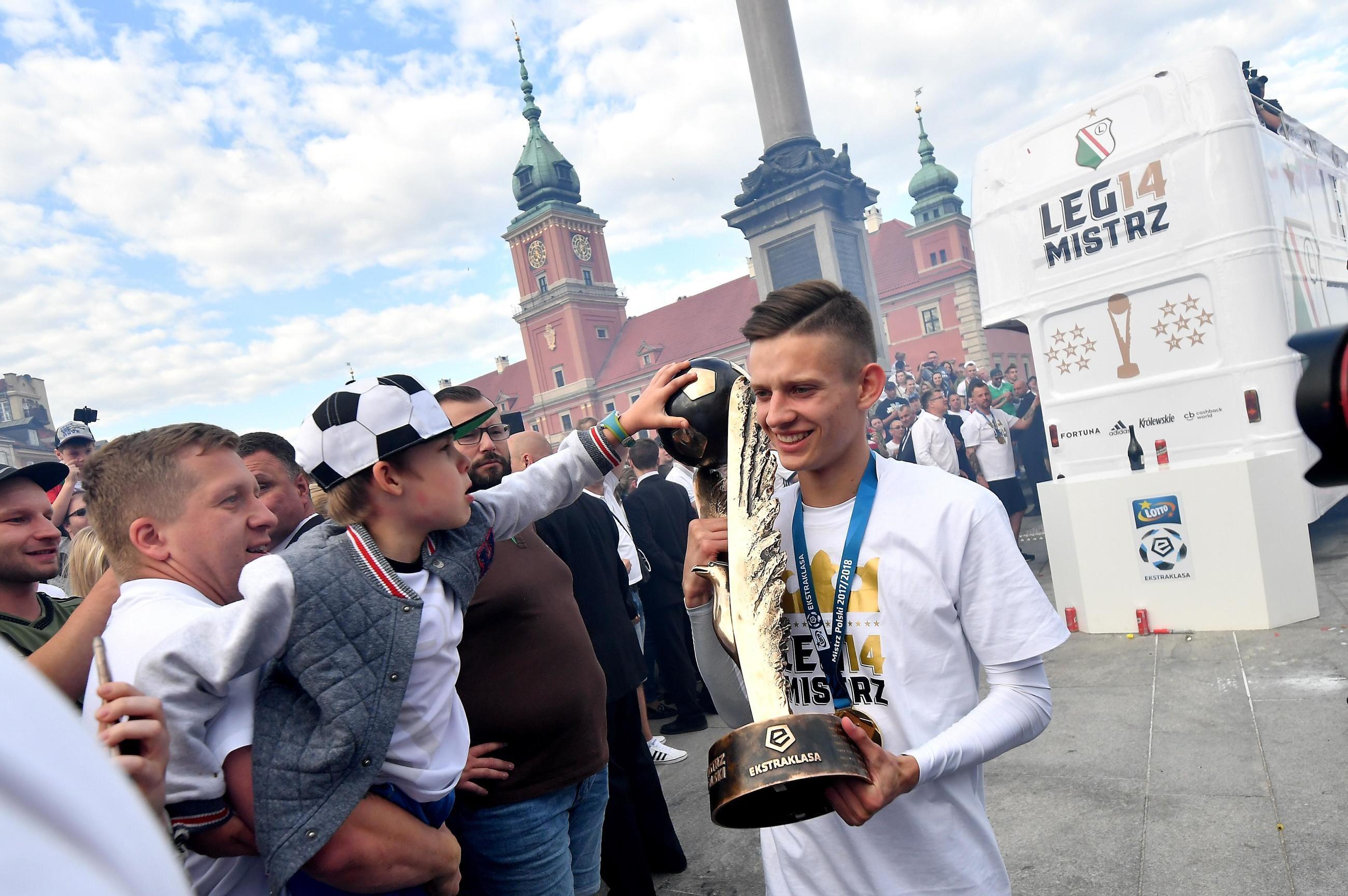 Piłkarz Legii Sebastian Szymański z mistrzowskim trofeum i kibicami